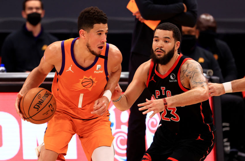 TAMPA, FLORIDA - MARCH 26: Devin Booker #1 of the Phoenix Suns drives on Fred VanVleet #23 of the Toronto Raptors (Photo by Mike Ehrmann/Getty Images)