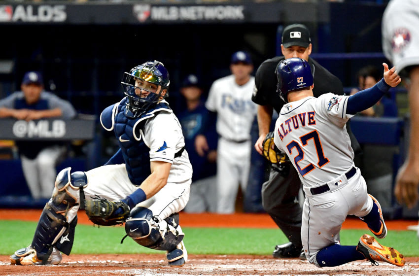 ST PETERSBURG, FLORIDA - OCTOBER 08: Jose Altuve #27 of the Houston Astros is tagged out at home plate by Travis d'Arnaud #37 of the Tampa Bay Rays while attempting to score a run during the fourth inning in game four of the American League Division Series at Tropicana Field on October 08, 2019 in St Petersburg, Florida. (Photo by Julio Aguilar/Getty Images)