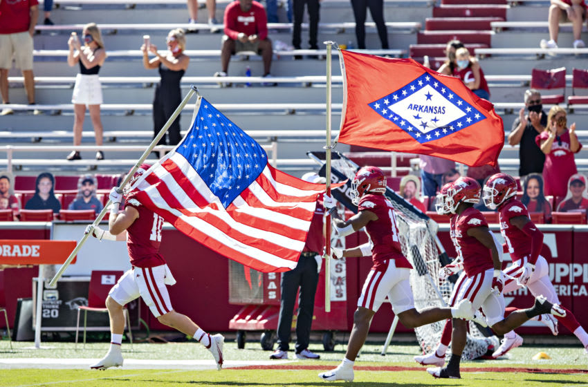 FAYETTEVILLE, AR - SEPTEMBER 26: Players of the Arkansas Razorbacks run onto the field with the American and Arkansas flag before a game against the Georgia Bulldogs at Razorback Stadium on September 26, 2020 in Fayetteville, Arkansas The Bulldogs defeated the Razorbacks 37-10. (Photo by Wesley Hitt/Getty Images)
