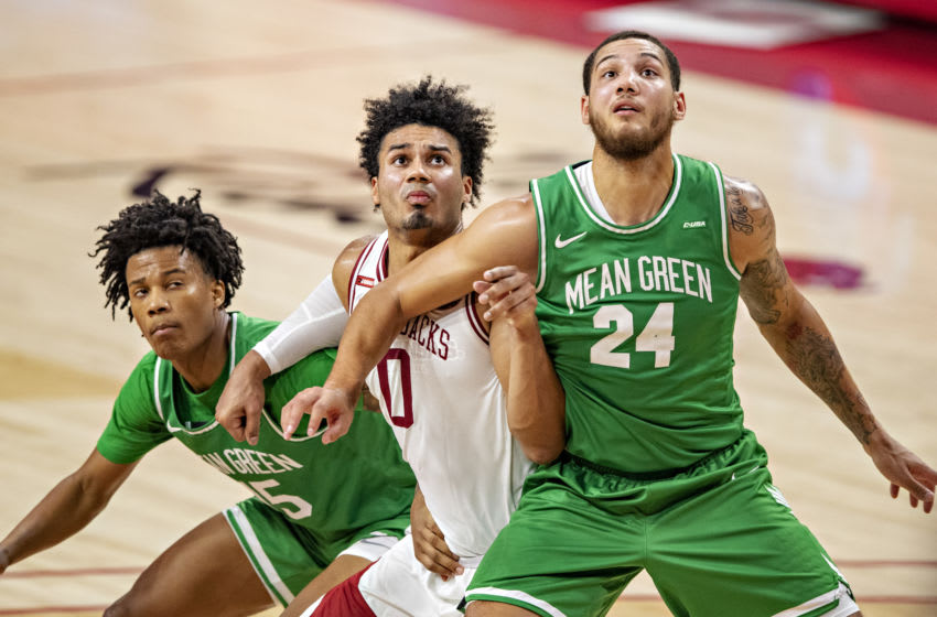 FAYETTEVILLE, AR - NOVEMBER 28: Justin Smith #0 of the Arkansas Razorbacks fights for a rebound against Rubin Jones #15 and Zachary Simmons #24 of the North Texas Mean Green at Bud Walton Arena on November 28, 2020 in Fayetteville, Arkansas. The Razorbacks defeated the Mean Green 69-54. (Photo by Wesley Hitt/Getty Images)