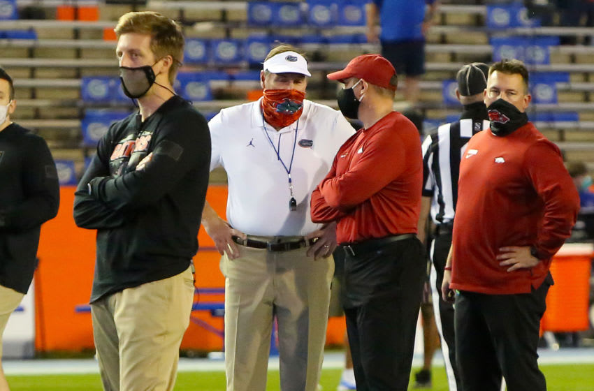 Nov 14, 2020; Gainesville, FL, USA; Florida Gators head coach Dan Mullen talks with Arkansas acting head coach Barry Odom before a football game at Ben Hill Griffin Stadium. Mandatory Credit: Brad McClenny-USA TODAY NETWORK