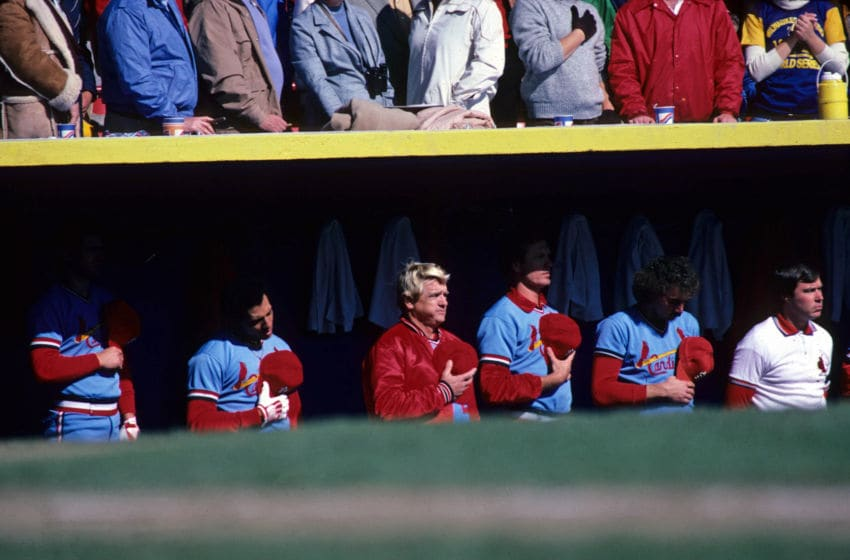 MILWAUKEE, WI - OCTOBER 15: Dane Iorg, Joaquin Andujar, manager Whitey Herzog, Bob Forch, Mike Ramsey, and trainer Gene Gieselmann of the St. Louis Cardinals stand for the national anthem before Game 3 of the World Series on October 15, 1982 at Milwaukee County Stadium in Milwaukee, Wisconsin. (Photo by St. Louis Cardinals, LLC/Getty Images)