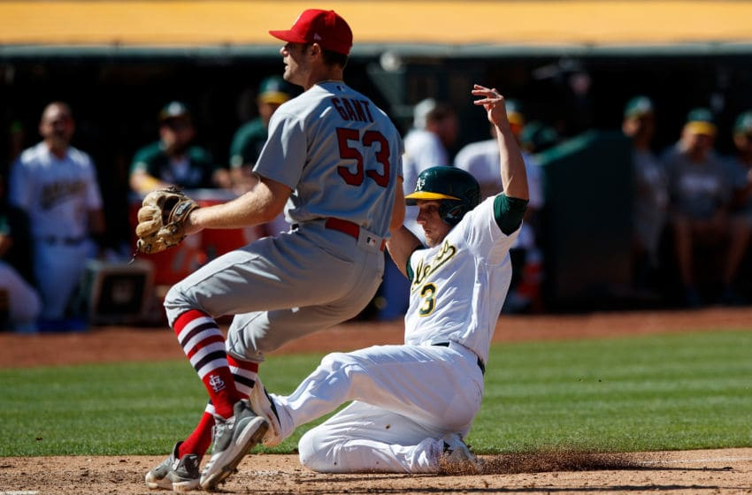 OAKLAND, CA - AUGUST 04: Dustin Garneau #3 of the Oakland Athletics scores a run past John Gant #53 of the St. Louis Cardinals during the eighth inning at the RingCentral Coliseum on August 4, 2019 in Oakland, California. The Oakland Athletics defeated the St. Louis Cardinals 4-2. (Photo by Jason O. Watson/Getty Images)