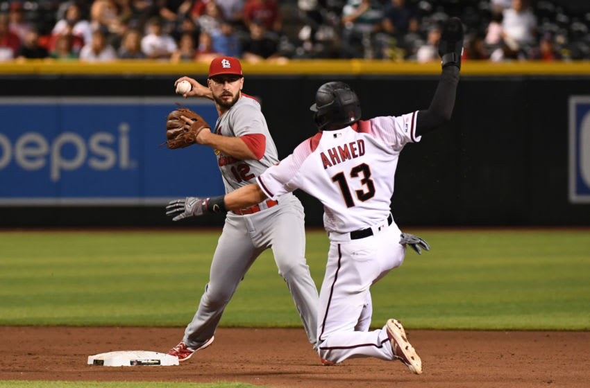 PHOENIX, ARIZONA - SEPTEMBER 23: Paul DeJong #12 of the St. Louis Cardinals turns a double play on a ground ball hit by Abraham Almonte #48 of the Arizona Diamondbacks as Nick Ahmed #13 slides into second base during the sixth inning at Chase Field on September 23, 2019 in Phoenix, Arizona. (Photo by Norm Hall/Getty Images)