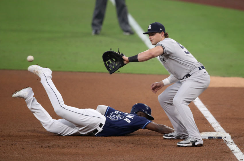 SAN DIEGO, CALIFORNIA - OCTOBER 05: Randy Arozarena #56 of the Tampa Bay Rays dives back to first to beat the throw to Luke Voit #59 of the New York Yankees in Game One of the American League Division Series at PETCO Park on October 05, 2020 in San Diego, California. (Photo by Christian Petersen/Getty Images)