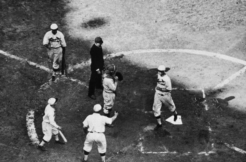 American baseball player infielder Andy High (1897 - 1981) of the St. Louis Cardinals (third from left) raises a hand to greet teammate outfielder George Watkins (1900 - 1970) as he comes across home plate after hitting a home run during game seven of the 1931 World Series against the Philadelphia Athletics, Sportsman's Park IV, St. Louis, October 10, 1931. The Cardinals won the game 4-2 to take the series. (Photo by Hulton Archive/Getty Images)