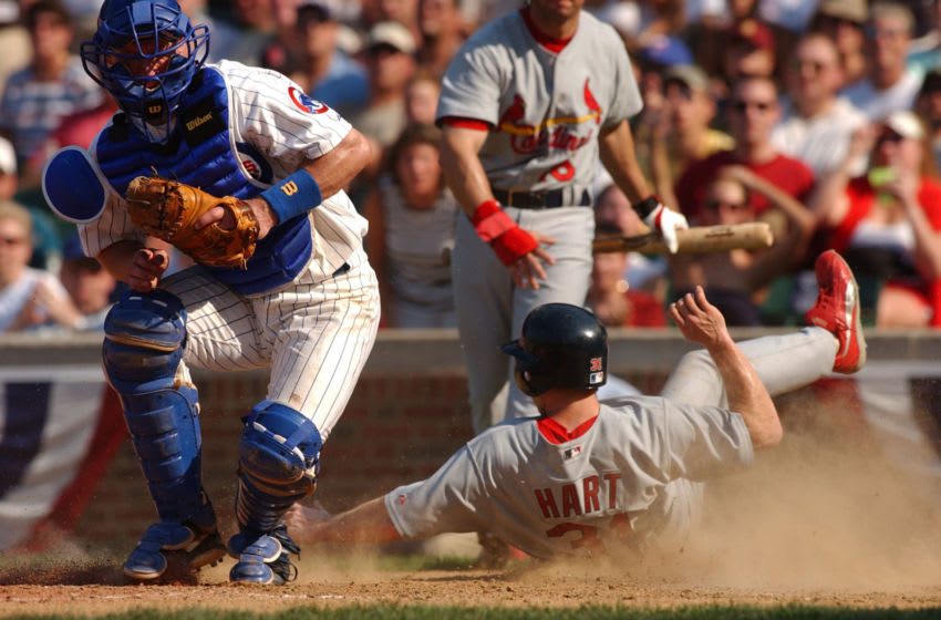 CHICAGO - JULY 4: Second baseman Bo Hart #31 of the St. Louis Cardinals slides into home ahead of a tag attempt by catcher Daimian Miller #27 of the Chicago Cubs in the eighh inning of a game on July 4, 2003 at Wrigley Field in Chicago, Illinois. The Cardinals defeated the Cubs 11-8. (Photo by Jonathan Daniel/Getty Images)