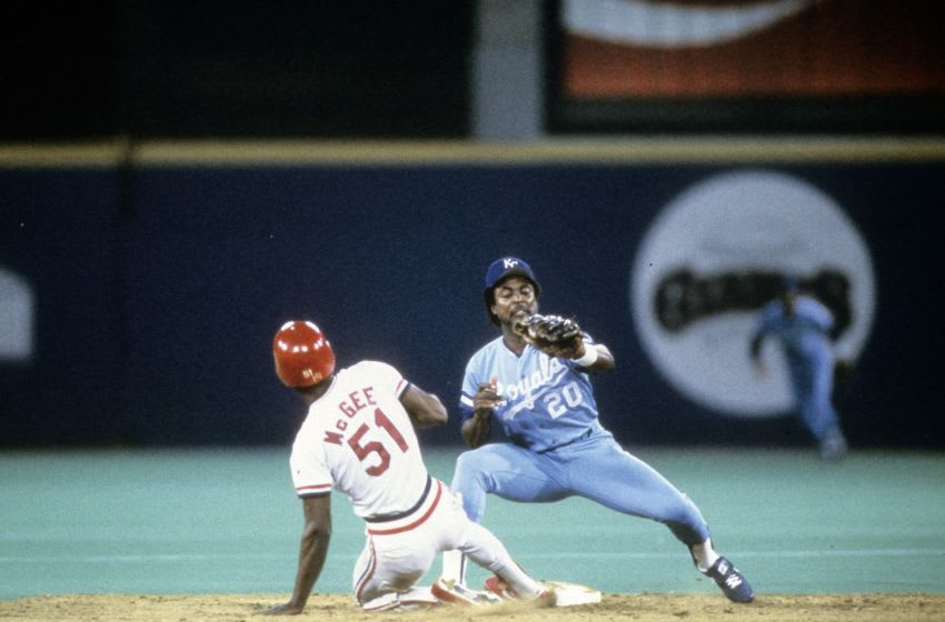 ST. LOUIS, MO - OCTOBER 1985: Outfielder Willie McGee #51 slides into second base while second baseman Frank White #20 receives the throw during the World Series at Busch Stadium in October 1985 in St. Louis, Missouri. The Royals won the World Series 4 games to 3. (Photo by Focus on Sport/Getty Images)