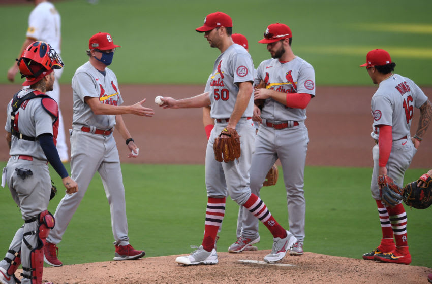 Oct 1, 2020; San Diego, California, USA; St. Louis Cardinals manager Mike Shildt (second from left) takes the ball from starting pitcher Adam Wainwright (50) during the fourth inning against the San Diego Padres at Petco Park. Mandatory Credit: Orlando Ramirez-USA TODAY Sports