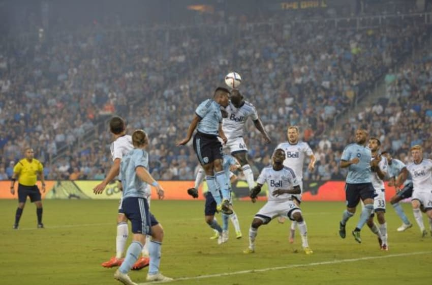 Aug 15, 2015; Kansas City, KS, USA; Sporting KC defender Soni Mustivar (93) heads the ball against Vancouver Whitecaps FC defender Pa-Kah (44) during the second half at Sporting Park. Mandatory Credit: Peter G. Aiken-USA TODAY Sports