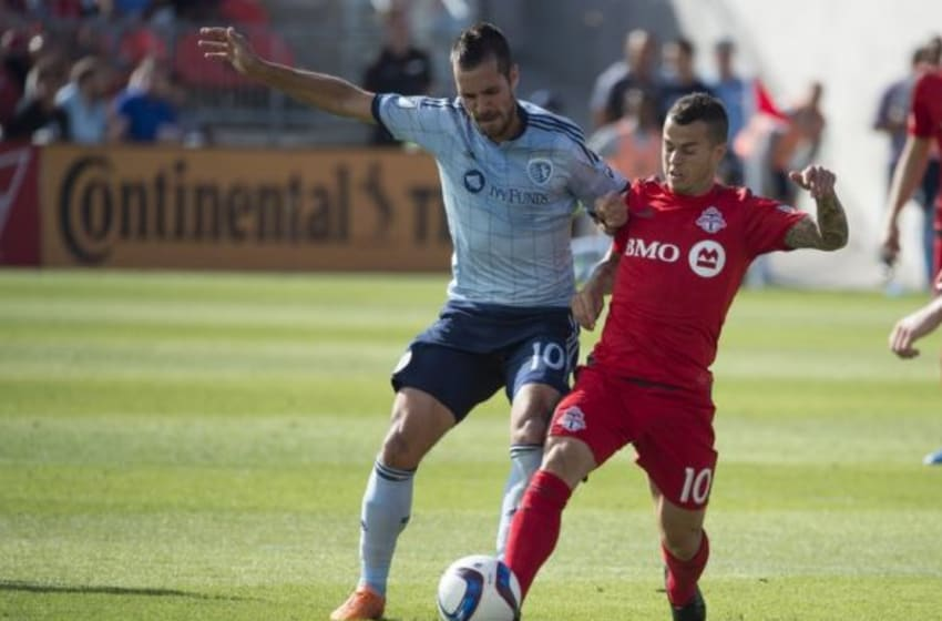 Aug 8, 2015; Toronto, Ontario, CAN; Toronto FC midfielder Sebastian Giovinco (10) battles for a ball with Sporting KC midfielder Benny Feilhaber (10) during the second half in a game at BMO Field. Sporting KC won 3-1. Mandatory Credit: Nick Turchiaro-USA TODAY Sports