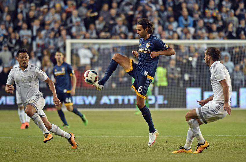 May 1, 2016; Kansas City, KS, USA; LA Galaxy mid-fielder Baggio Husidic (6) traps the ball against Sporting KC defender Nuno Coelho (12) during the second half at Children