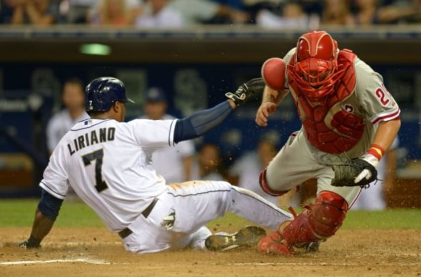 Sep 16, 2014; San Diego, CA, USA; San Diego Padres right fielder Rymer Liriano (7) slides safely passed Philadelphia Phillies catcher Cameron Rupp (right) on a single by second baseman Jedd Gyorko (not pictured) during the sixth inning at Petco Park. Mandatory Credit: Jake Roth-USA TODAY Sports