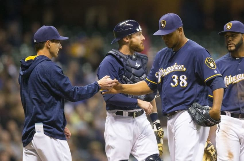 Apr 9, 2016; Milwaukee, WI, USA; Milwaukee Brewers pitcher Wily Peralta (38) hands the baseball to manager Craig Counsell (30) after being pulled from the game during the fifth inning against the Houston Astros at Miller Park. Mandatory Credit: Jeff Hanisch-USA TODAY Sports
