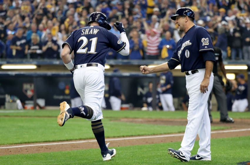 MILWAUKEE, WI - OCTOBER 13: Travis Shaw #21 of the Milwaukee Brewers celebrates with third base coach Ed Sedar #0 after hitting a solo home run against Alex Wood #57 of the Los Angeles Dodgers during the sixth inning in Game Two of the National League Championship Series at Miller Park on October 13, 2018 in Milwaukee, Wisconsin. (Photo by Rob Carr/Getty Images)