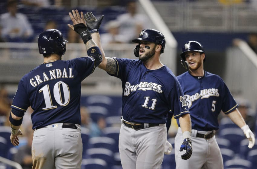 MIAMI, FLORIDA - SEPTEMBER 11: Mike Moustakas #11 of the Milwaukee Brewers celebrates with Yasmani Grandal #10 and Cory Spangenberg #5 after hitting a three-run home run in the third inning against the Miami Marlins at Marlins Park on September 11, 2019 in Miami, Florida. (Photo by Michael Reaves/Getty Images)