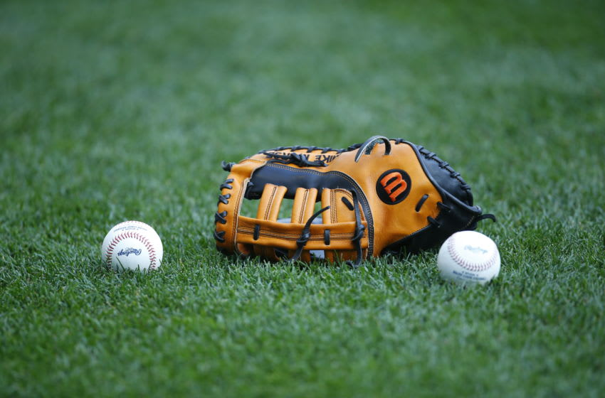 MILWAUKEE, WI - SEPTEMBER 03: A Wilson baseball glove and major league baseballs sits on the field at Miller Park on September 3, 2015 in Milwaukee, Wisconsin. (Photo by Jeff Haynes/Getty Images)