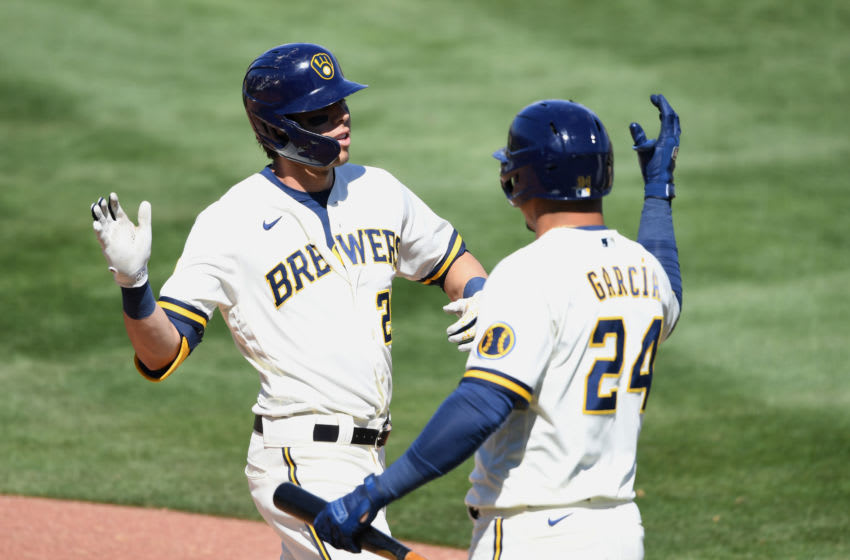 PHOENIX, ARIZONA - MARCH 24: Christian Yelich #22 of the Milwaukee Brewers celebrates with Avisail Garcia #24 after hitting a grand slam home run off of Jon Gray #55 of the Colorado Rockies during the third inning of a spring training game at American Family Fields of Phoenix on March 24, 2021 in Phoenix, Arizona. (Photo by Norm Hall/Getty Images)