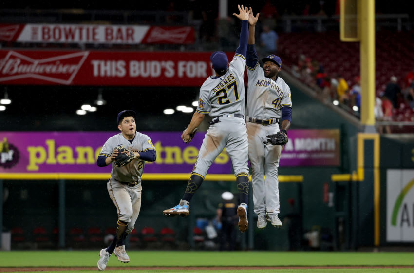 CINCINNATI, OHIO - JUNE 08: Luis Urias #2, Willy Adames #27, and Jackie Bradley Jr. #41 of the Milwaukee Brewers celebrate after beating the Cincinnati Reds 5-1 at Great American Ball Park on June 08, 2021 in Cincinnati, Ohio. (Photo by Dylan Buell/Getty Images)