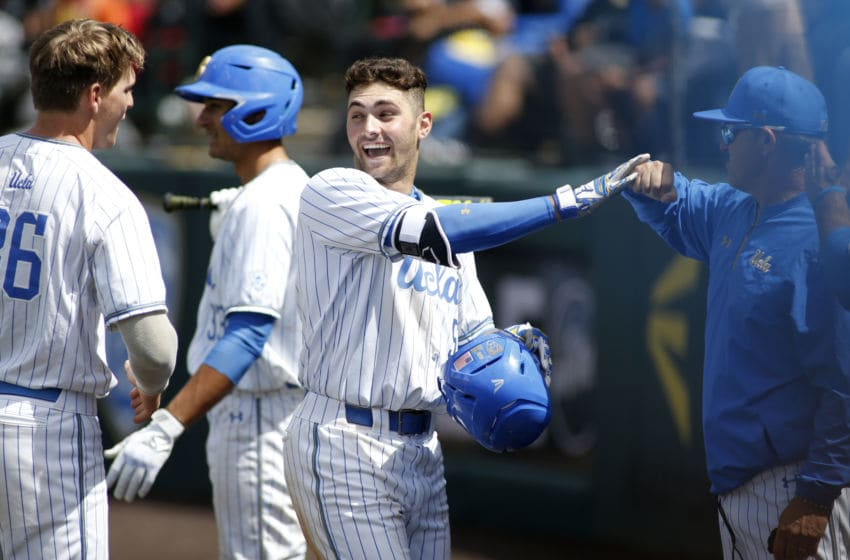 LOS ANGELES, CALIFORNIA - MAY 19: Garrett Mitchell #5 of UCLA fist-bumps a coach as he makes his way to the dugout following his home run during a baseball game against University of Washington at Jackie Robinson Stadium on May 19, 2019 in Los Angeles, California. (Photo by Katharine Lotze/Getty Images)