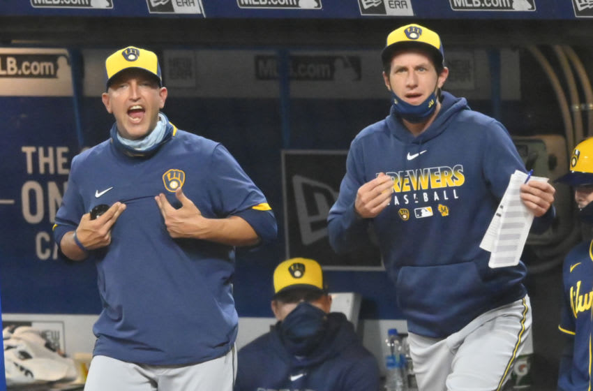 Sep 4, 2020; Cleveland, Ohio, USA; Milwaukee Brewers hitting coach Andy Haines (49), left and manager Craig Counsell (30) react to a strike call in the seventh inning against the Cleveland Indians at Progressive Field. Haines was ejected from the game. Mandatory Credit: David Richard-USA TODAY Sports