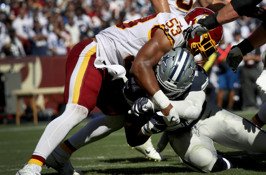 LANDOVER, MARYLAND - SEPTEMBER 15: Running back Ezekiel Elliott #21 of the Dallas Cowboys crosses the goal line for a touchdown as linebacker Jon Bostic #53 of the Washington Football Team tries to stop him during second half action against the Washington Redskins at FedExField on September 15, 2019 in Landover, Maryland. The Cowboys won the game 31-21. (Photo by Win McNamee/Getty Images)