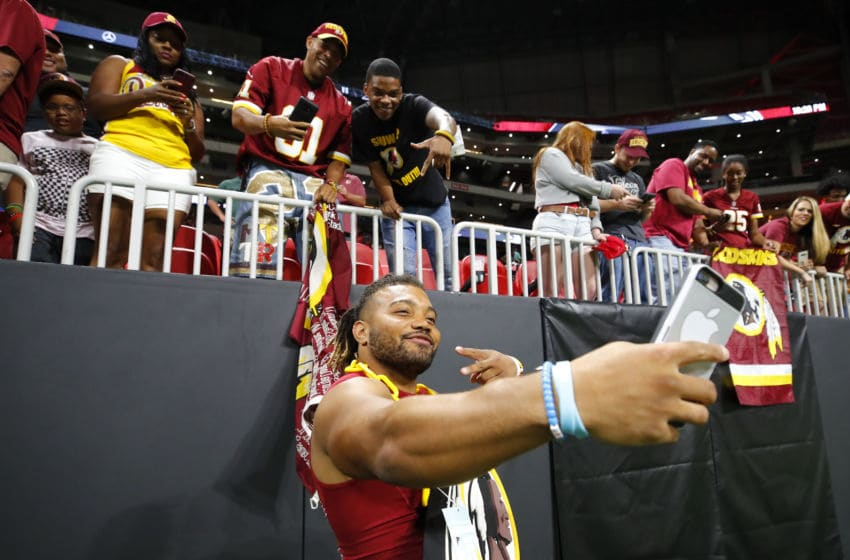 ATLANTA, GA - AUGUST 22: Derrius Guice #29 of the Washington Redskins takes selfies with fans at the conclusion of an NFL preseason game against the Atlanta Falcons at Mercedes-Benz Stadium on August 22, 2019 in Atlanta, Georgia. (Photo by Todd Kirkland/Getty Images)