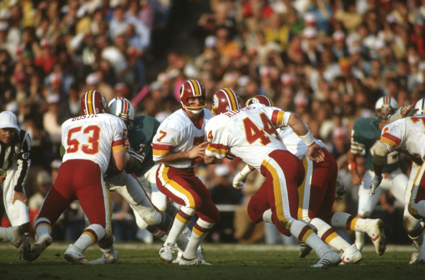 PASADENA, CA - JANUARY 30: Joe Theismann #7 of the Washington Redskins turns to hand the ball off to running back John Riggins #44 against the Miami Dolphins during Super Bowl XVII on January 30, 1983 at the Rose Bowl in Pasadena, California. The Redskins won the Super Bowl 27-17. (Photo by Focus on Sport/Getty Images)