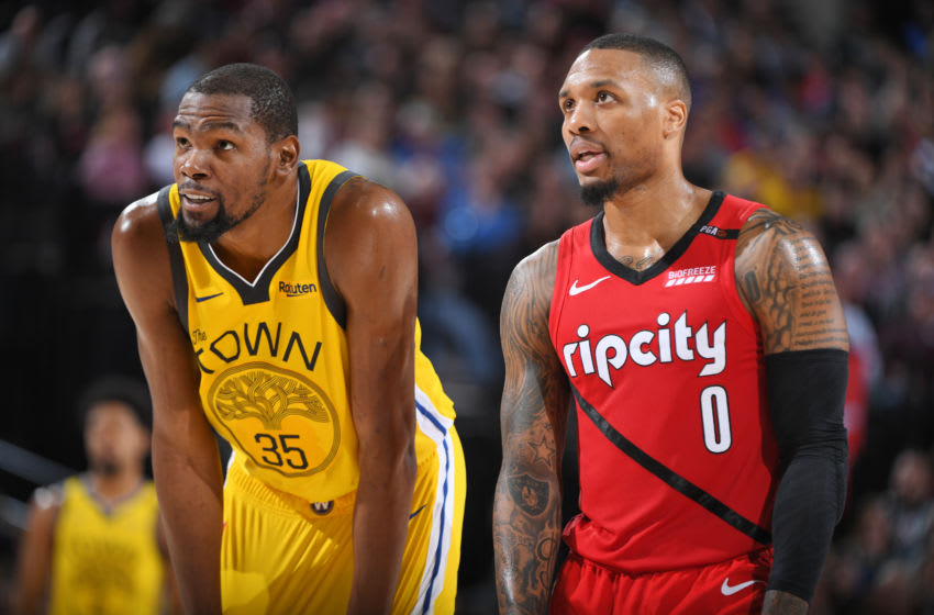 Kevin Durant #35 of the Golden State Warriors and Damian Lillard #0 of the Portland Trail Blazers look on during the game on December 29, 2018 at the Moda Center Arena in Portland, Oregon. (Photo by Garrett Ellwood/NBAE via Getty Images)