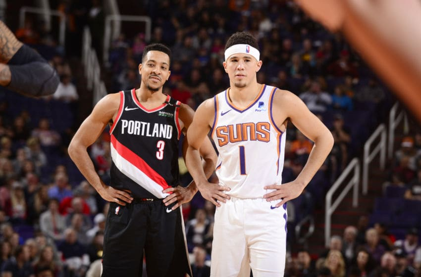 PHOENIX, AZ - JANUARY 24: CJ McCollum #3 of the Portland Trail Blazers and Devin Booker #1 of the Phoenix Suns look on during the game on January 24, 2019 at Talking Stick Resort Arena in Phoenix, Arizona. NOTE TO USER: User expressly acknowledges and agrees that, by downloading and or using this photograph, user is consenting to the terms and conditions of the Getty Images License Agreement. Mandatory Copyright Notice: Copyright 2019 NBAE (Photo by Barry Gossage/NBAE via Getty Images)