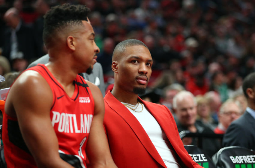 PORTLAND, OREGON - FEBRUARY 25: Damian Lillard #0 reacts alongside CJ McCollum #3 of the Portland Trail Blazers in the first quarter against the Boston Celtics during their game at Moda Center on February 25, 2020 in Portland, Oregon. NOTE TO USER: User expressly acknowledges and agrees that, by downloading and or using this photograph, User is consenting to the terms and conditions of the Getty Images License Agreement. (Photo by Abbie Parr/Getty Images)