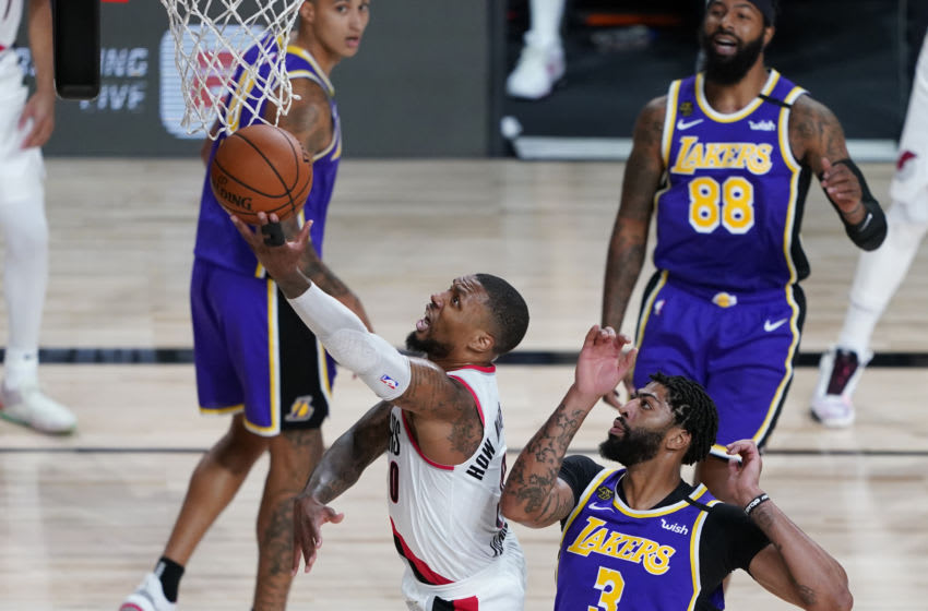 LAKE BUENA VISTA, FLORIDA - AUGUST 22: Damian Lillard #0 of the Portland Trail Blazers drives to the basket past Anthony Davis #3 of the Los Angeles Lakers during the first half of Game Three of the first round of the playoffs between the Los Angeles Lakers and the Portland Trail Blazers at the AdventHealth Arena at the ESPN Wide World Of Sports Complex on August 22, 2020 in Lake Buena Vista, Florida. NOTE TO USER: User expressly acknowledges and agrees that, by downloading and or using this photograph, User is consenting to the terms and conditions of the Getty Images License Agreement. (Photo by Ashley Landis-Pool/Getty Images)