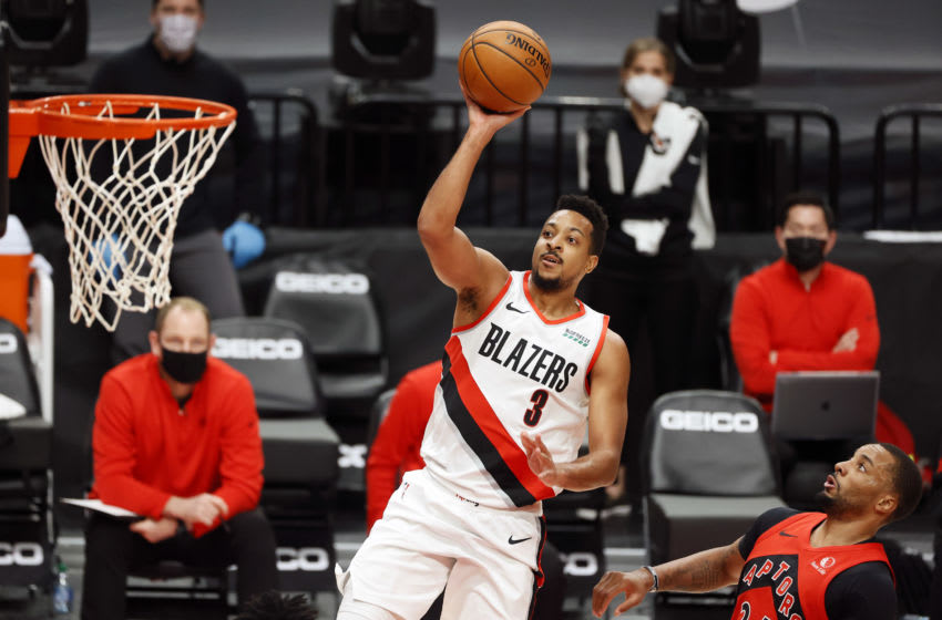 Jan 11, 2021; Portland, Oregon, USA; Portland Trail Blazers shooting guard CJ McCollum (3) shoots the ball past Toronto Raptors shooting guard Norman Powell (R) during the first half at Moda Center. Mandatory Credit: Soobum Im-USA TODAY Sports