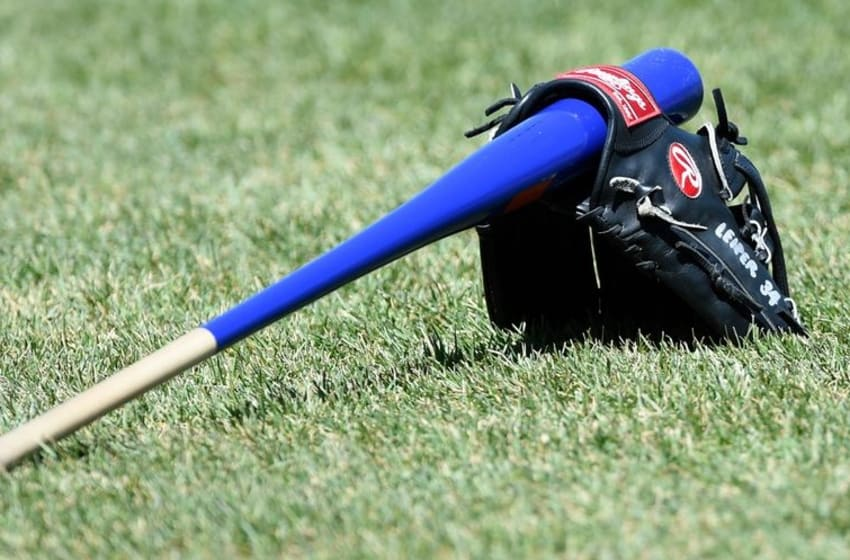 Apr 16, 2016; Boston, MA, USA; The glove and bat of Toronto Blue Jays first base coach Tim Leiper (34) rests on the grass prior to a game against the Boston Red Sox at Fenway Park. Mandatory Credit: Bob DeChiara-USA TODAY Sports
