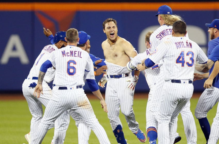 NEW YORK, NY - AUGUST 09: Teammates mob Michael Conforto #30 of the New York Mets and tear off his shirt as they celebrate winning the game after Conforto hit a walk off rbi single to win the game in the bottom of the ninth inning in an MLB baseball game against the Washington Nationals on August 9, 2019 at Citi Field in the Queens borough of New York City. Mets won 7-6. (Photo by Paul Bereswill/Getty Images)
