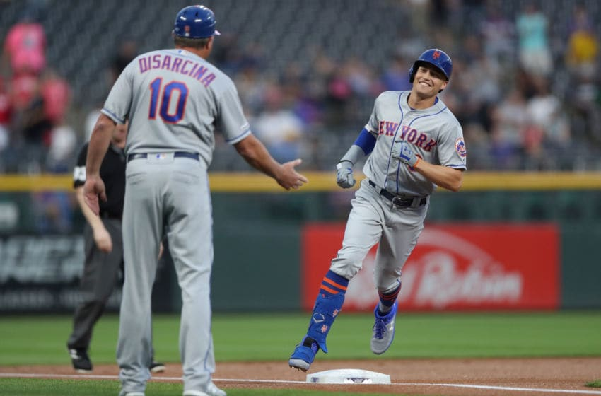 DENVER, COLORADO - SEPTEMBER 16: Brandon Nimmo #9 of the New York Mets is congratulated by third base coach Gary DiSarcina #10 as he rounds the bases after hitting a lead of home run in the first inning against the Colorado Rockies at Coors Field on September 16, 2019 in Denver, Colorado. (Photo by Matthew Stockman/Getty Images)