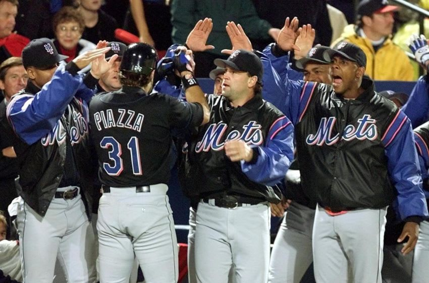 Catcher Mike Piazza (31) of the New York Mets is greeted by teammates after his two-run home run in the 7th inning to tie the game against the Atlanta Braves 19 October, 1999, during game 6 of the National League Championship Series at Turner Field in Atlanta, GA. The Braves lead the the best-of-seven- series 3-2. (ELECTRONIC IMAGE) AFP PHOTO/JEFF HAYNES (Photo by JEFF HAYNES / AFP) (Photo by JEFF HAYNES/AFP via Getty Images)