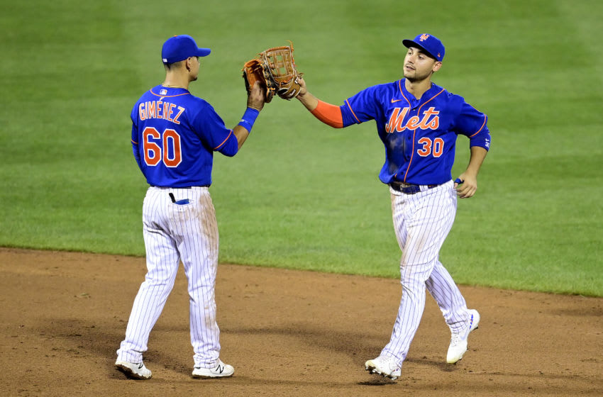 NEW YORK, NEW YORK - AUGUST 12: Andres Gimenez #60 and Michael Conforto #30 of the New York Mets slap gloves as they celebrate an 11-6 win against the Washington Nationals at Citi Field on August 12, 2020 in New York City. (Photo by Steven Ryan/Getty Images)