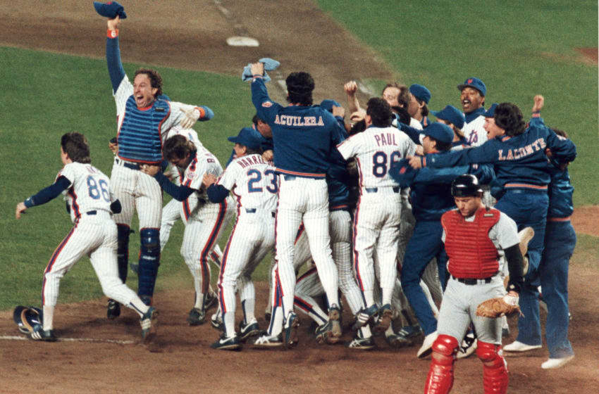 Members of the New York Mets baseball team celebrate their victory in game six of the World Series at Shea Stadium, Flushing, New York, October 25, 1986. They went on to defeat the Boston Red Sox in the series four games to three. Visible players include Mets catcher Gary Carter (at left with arm raised), and teammates Wally Backman (who hugs Carter), coach Bud Harrelson (#23), and Rick Aguilera; Red Sox catcher Rich Gedman (at right, in red uniform) walks way dejectedly. (Photo by Robert Riger/Getty Images)