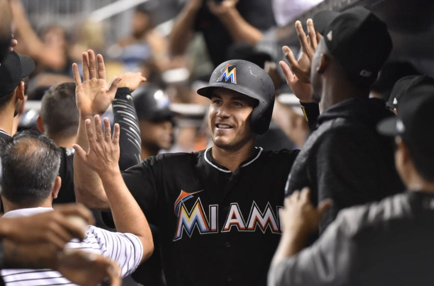 MIAMI, FL - JULY 28: J.T. Realmuto #11 of the Miami Marlins is congratulated by teammates after scoring on a sacrifice fly by Yadiel Rivera #2 during the fourth inning of the game against the Washington Nationals at Marlins Park on July 28, 2018 in Miami, Florida. (Photo by Eric Espada/Getty Images)