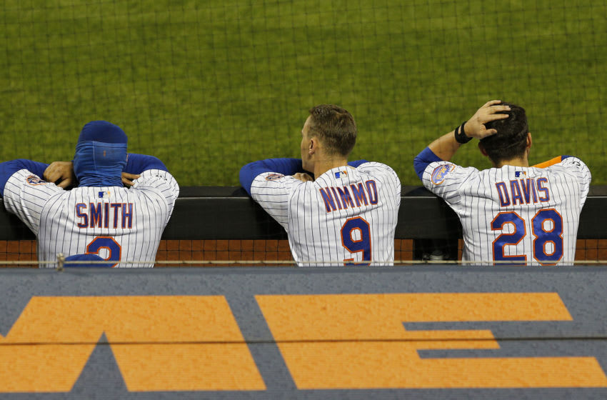 Sep 21, 2020; New York City, New York, USA; New York Mets first baseman Dominic Smith (2) right fielder Brandon Nimmo (9) and third baseman J.D. Davis (28) look on from the dugout against the Tampa Bay Rays during the ninth inning at Citi Field. Mandatory Credit: Andy Marlin-USA TODAY Sports