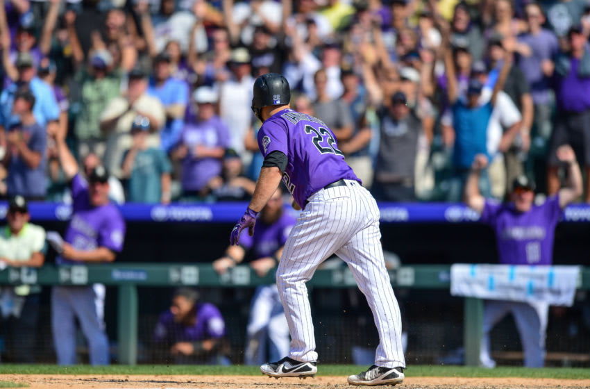 DENVER, CO - AUGUST 12: Chris Iannetta #22 of the Colorado Rockies walks to first base on a bases-loaded walk-off walk as teammates and fans react in the bottom of the ninth inning of a game against the Los Angeles Dodgers at Coors Field on August 12, 2018 in Denver, Colorado. (Photo by Dustin Bradford/Getty Images)