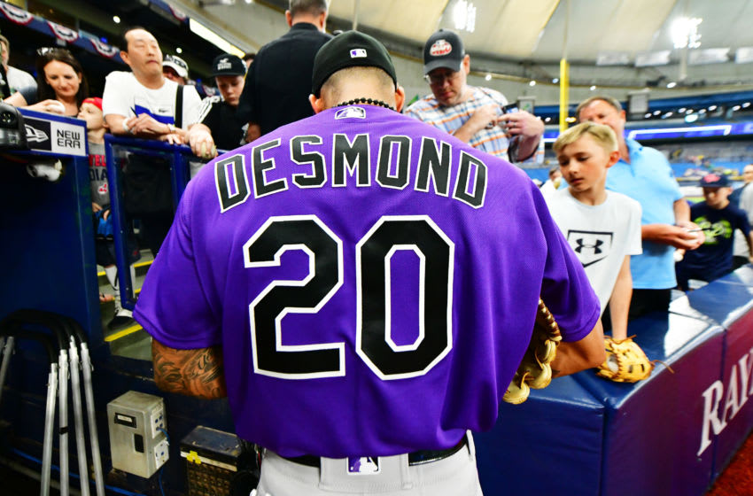 ST PETERSBURG, FLORIDA - APRIL 02: Ian Desmond #20 of the Colorado Rockies signs autographs for fans before a game against the Tampa Bay Rays at Tropicana Field on April 02, 2019 in St Petersburg, Florida. (Photo by Julio Aguilar/Getty Images)