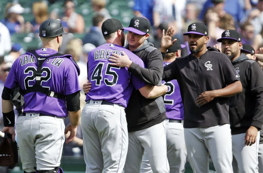CHICAGO, ILLINOIS - JUNE 06: Scott Oberg #45 of the Colorado Rockies gets a hug from Peter Lambert #23 following their team's 3-1 win over the Chicago Cubs at Wrigley Field on June 06, 2019 in Chicago, Illinois. (Photo by Nuccio DiNuzzo/Getty Images)