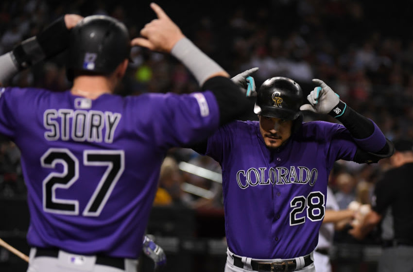 PHOENIX, ARIZONA - AUGUST 20: Nolan Arenado #28 of the Colorado Rockies celebrates with Trevor Story #27 after Arenado's two-run home run off of Alex Young of the Arizona Diamondbacks during the fourth inning at Chase Field on August 20, 2019 in Phoenix, Arizona. Arenado was playing in his 1,000th MLB game. (Photo by Norm Hall/Getty Images)