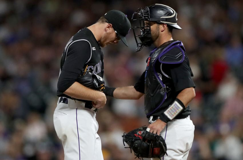 DENVER, COLORADO - SEPTEMBER 13: Catcher Drew Butera #25 and starting pitcher Jeff Hoffman #34 of the Colorado Rockies confer in the fifth inning against the San Diego Padres at Coors Field on September 13, 2019 in Denver, Colorado. (Photo by Matthew Stockman/Getty Images)