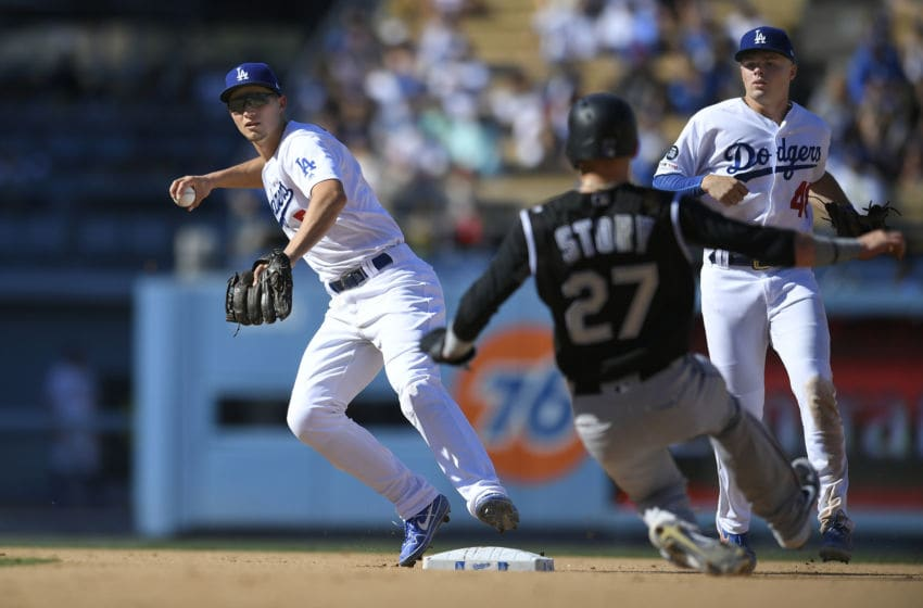LOS ANGELES, CA - SEPTEMBER 22: Corey Seager #5 of the Los Angeles Dodgers throws to first from second as he catches Trevor Story #27 of the Colorado Rockies in a double play and Gavin Lux #48 looks on in th eighth inning at Dodger Stadium on September 22, 2019 in Los Angeles, California. The Dodgers won 7-4. (Photo by John McCoy/Getty Images)