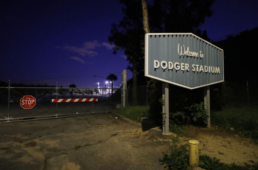 LOS ANGELES, CALIFORNIA - MARCH 26: A sign for Dodger Stadium stands next to a locked gate on what was supposed to be Major League Baseball's opening day, now postponed due to the coronavirus, on March 26, 2020 in Los Angeles, California. The Los Angeles Dodgers were slated to play against the San Francisco Giants at the stadium today. Major League Baseball Commissioner Rob Manfred recently said the league is