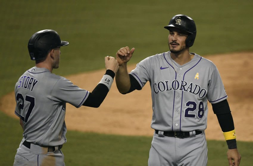 LOS ANGELES, CA - SEPTEMBER 05: Nolan Arenado #28 and Trevor Story #27 of the Colorado Rockies celebrate after scoring on a double by Josh Fuentes #8 against relief pitcher Alex Wood #57 of the Los Angeles Dodgers during the ninth inning at Dodger Stadium on September 5, 2020 in Los Angeles, California. (Photo by Kevork Djansezian/Getty Images)