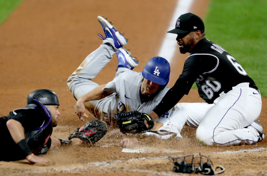 DENVER, COLORADO - SEPTEMBER 19: Austin Barnes #15 of the Los Angeles Dodgers scores against catcher Drew Butera #6 and pitcher Mychal Givens #60 of the Colorado Rockies on a wild pitch in the seventh inning at Coors Field on September 19, 2020 in Denver, Colorado. (Photo by Matthew Stockman/Getty Images)